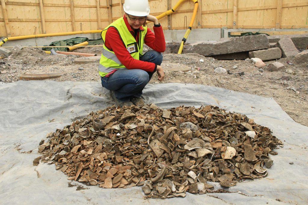 Kaivaustyöntekijä katselee isoa kasaa kaivauslöytöjä kaivaustyömaalla.