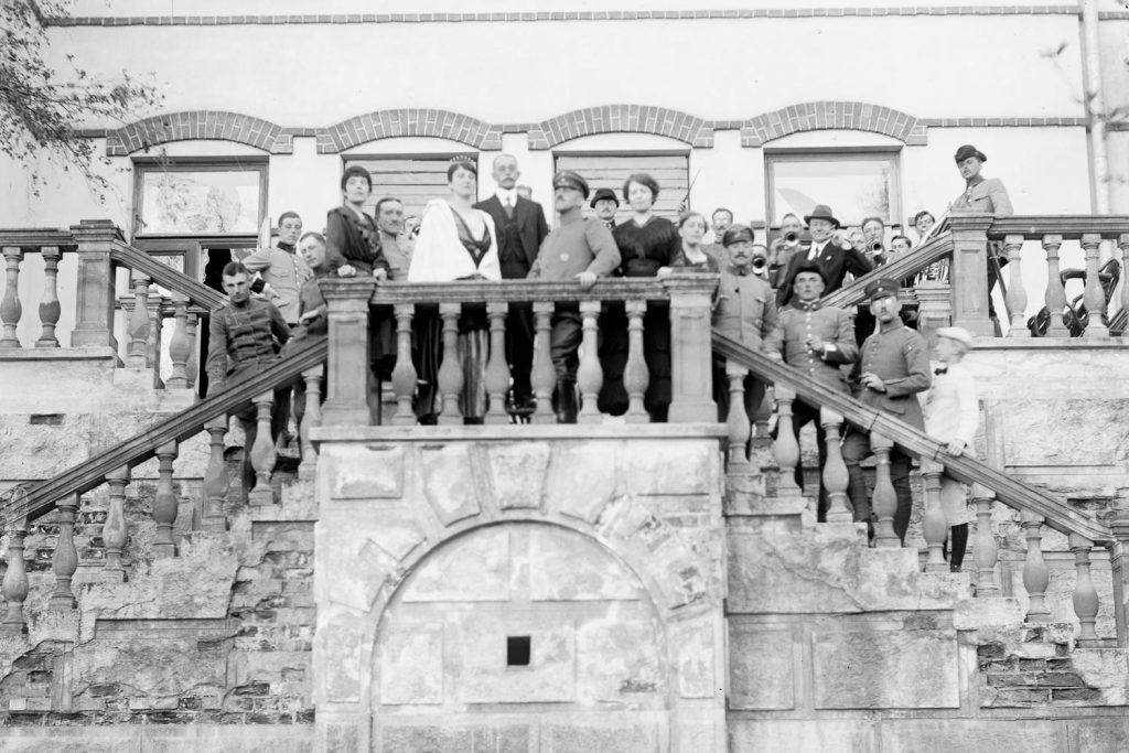 Väkijoukko poseeraa Kartanon portailla.