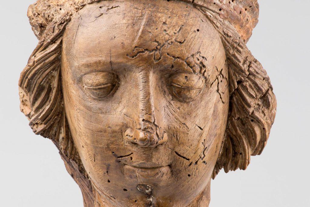 Puinen veistos, jossa kuvattuna ihmisen pää.