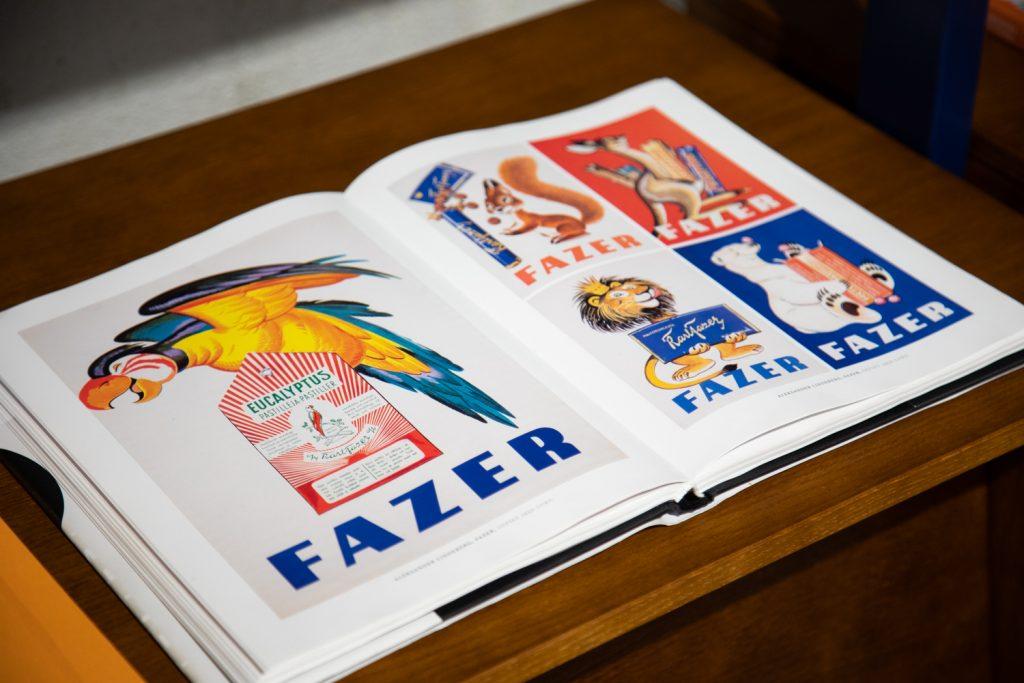 Avonainen kirja, jossa kuvia eläinaiheisista Fazerin makeisia markkinoivista julisteista. Papukaija pastillirasian päällä. Leijona pitelemässä suklaalevyä. Jääkarhu, Orava.