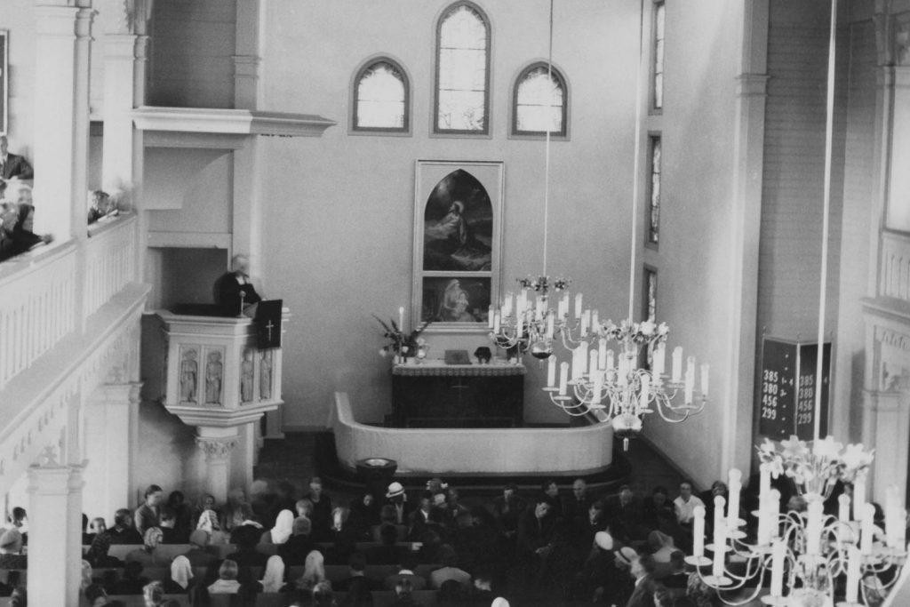 Vanha keski-Lahden kirkko. Näkymä parvelta. Alttari, saarnastuoli, virsitaulu, kattokruunut. Pappi puhuu kirkossa olevalle yleisölle.