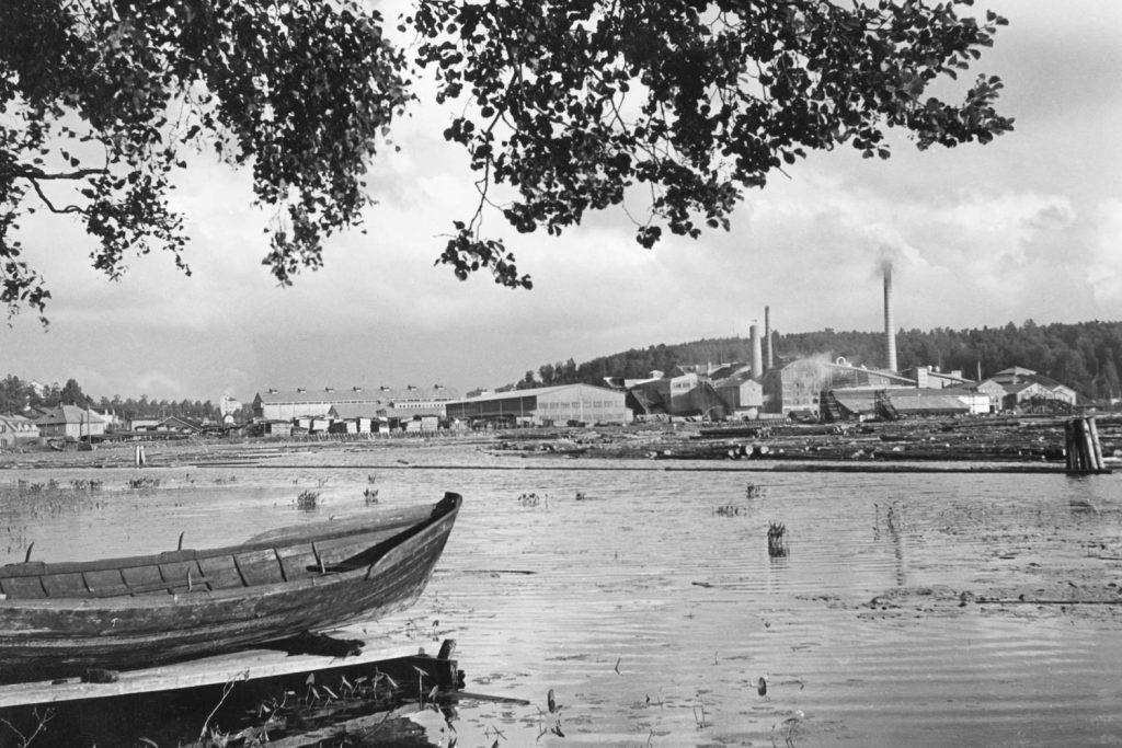 Vanha teollisuusalue. Etualalla vene Järven toisella puolen tehtaan piippuja.
