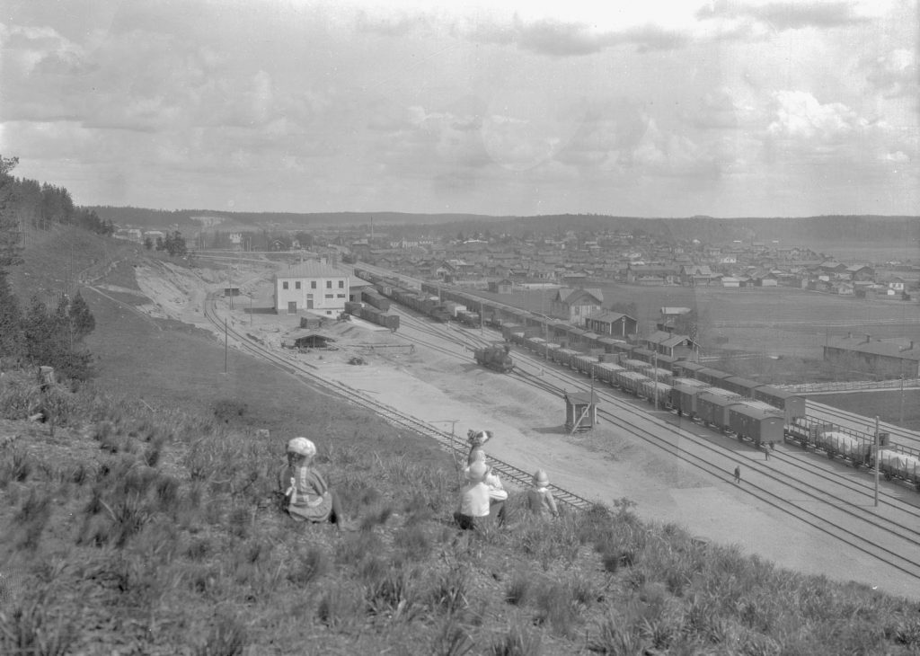 Lapset istuvat junaradan varrella olevalla mäellä, josta avautuu näkymä vanhaan Lahteen.