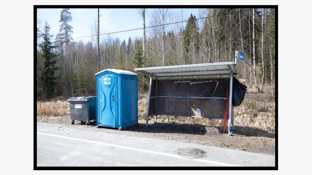 Roskakori, kuivakäymälä ja tyhjä bussipysäkki suljetulla Uudenmaan ja Päijät-Hämeen rajalla.