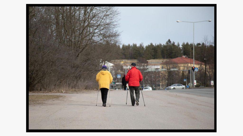 Kaksi sauvakävelemässä olevaa eläkeläistä kuvattuna selkäpuolelta Lahden Kivistönmäellä.