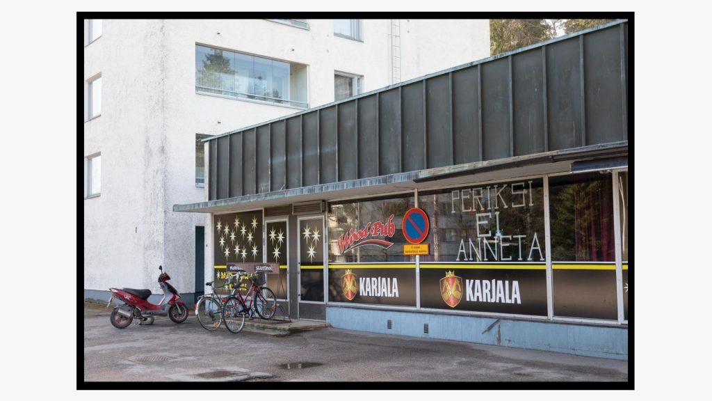 """Baarin ikkunaan on muotoiltu maalarinteipillä teksti: """"Periksi ei anneta""""."""