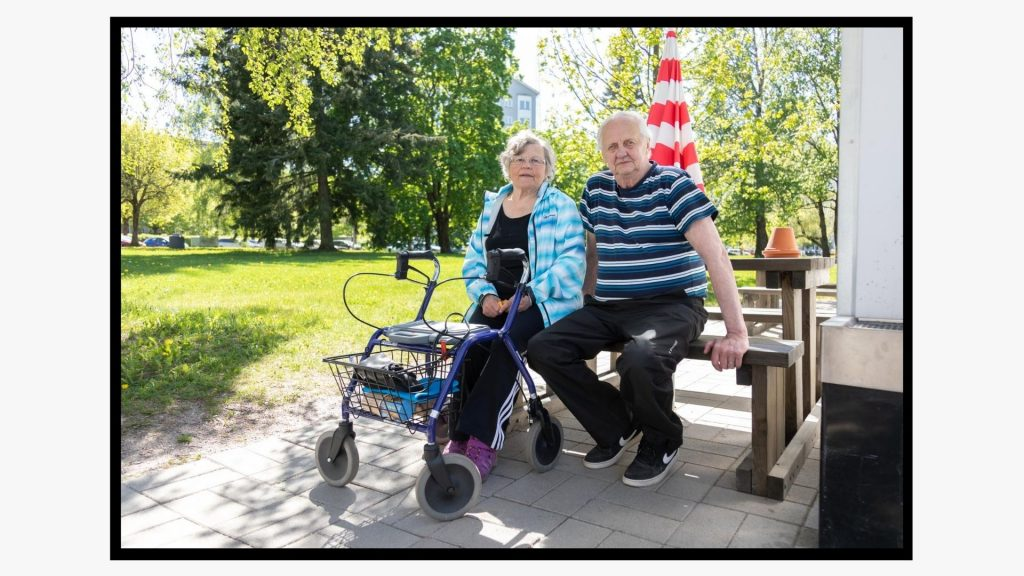 Eläkeläispariskunta istuu penkillä keväisenä päivänä.