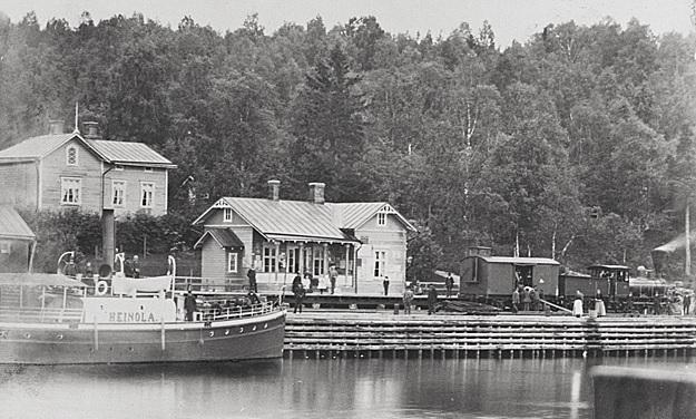 Rautatieasema Vesijärven rannalla. Etualalla järvi sekä laivoja.