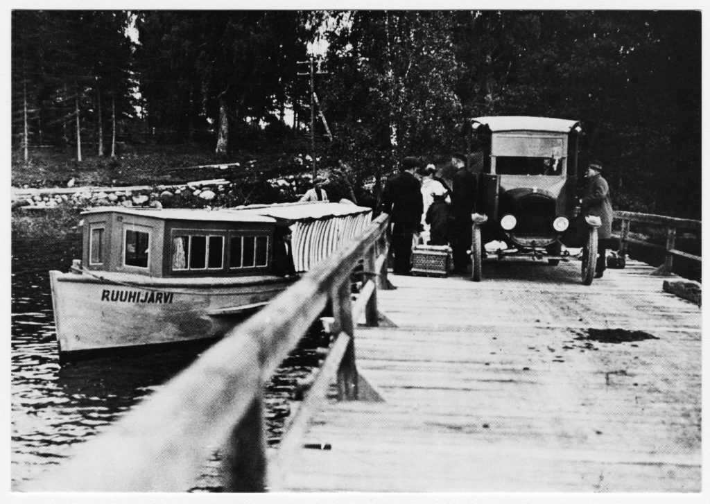 Laiva sillan vieressä pysähtyneenä. Sillalla auto.